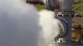 Zoom in considerazione di emissione di acqua termale, vapore dal pozzo geologico video d archivio