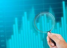 Zoom della lente d'ingrandimento su un grafico di affari Immagine Stock