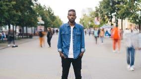 Zoom fuori al rallentatore del maschio afroamericano sollecitato che esamina macchina fotografica che sta nella via in metropoli  archivi video