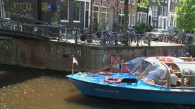 Zoom fuori e pentola dal crogiolo di canale a Amsterdam con le bandiere tipiche di Amsterdam stock footage