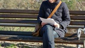 ZOOM FUORI su una lettura della giovane donna sul banco di parco Fortezza di Petrovaradin, Novi Sad, Serbia stock footage