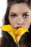 Zoom on a girls face with a yellow calla Royalty Free Stock Image