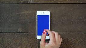 Zoom In Hand Smartphone with Blue Screen. Female Hand Using Vertical Smartphone with Blue Screen Zoom In on the Background of Wooden Table stock video
