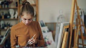 Zoom-i av den attraktiva kvinnan som framme står av staffli och målar med borsteinnehavpaletten i hand och ser arkivfilmer