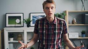 Zoom-i av den olyckliga unga mannen med den ilskna framsidan som klagar och uttrycker retning- och förseelseanseende i trevligt s arkivfilmer