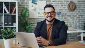 Zoom-i ståenden av den attraktiva grabben som använder bärbara datorn som ser därefter att le för kamera stock video