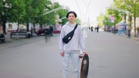 Zoom-i Time-schackningsperioden av skateboarderen som står i gatan med skateboarden bara arkivfilmer