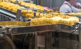 Zoom-in instant noodles on transmission belt in production Stock Photos