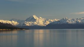 Zoom in on a lake and a snowy mt cook stock video footage