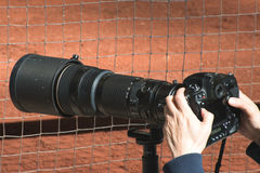 Zoom Lens, Professional Sports Photography. A professional photographer is photographing a sports event using a zoom camera lens Stock Photography