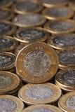 Zoom in moneda de diez pesos mexicanos sobre más monedas alineadas y apiladas, Toma vertical Stock Images