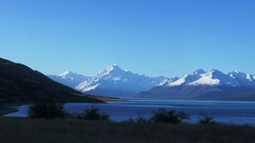 Zoom in on mt cook and lake at dusk. A zoom shot of mt cook and lake pukaki at dusk in new zealand stock video