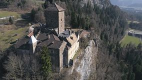 Zoom out castle aerial 4k. Aerial footage of a castle on the cliff in a valley with mountains in the background. Shot in Switzerland in 4k quality stock footage