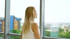 Zoom out of cheerful blonde woman looking out the window at cityscape. In slow motion. enjoying the moment and planning for future. people, privacy, emotion stock footage
