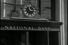 Zoom out clock to bank entrance on city street stock video footage