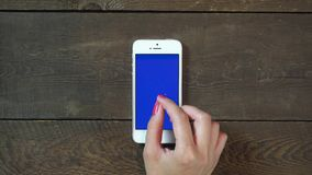 Zoom Out Hand Smartphone with Blue Screen. Female Hand Using Vertical Smartphone with Blue Screen Zoom Out on the Background of Wooden Table stock video footage