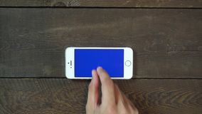 Zoom Out Hand Smartphone with Blue Screen stock video footage