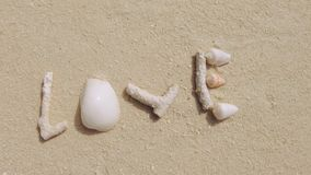 Zoom Out Of Love. Zoom Out Of The Word Love, Made Out Of Corals And Shells On White Beach Sand stock footage