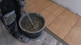 Zoom out of man mix cement tile glue on bucket stock video