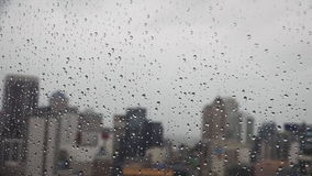Zoom out of rain drops falls on a window with Auckland CBD New Zealand. In the background on a stormy day stock video footage