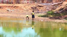Zoom out shot of two kids playing on water pond. Nature background stock video