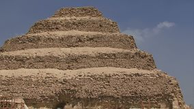 Zoom out from the step pyramid in Egypt. Step pyramid in Egypt with construction and repairs stock video footage