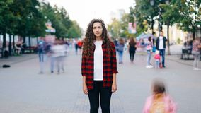 Zoom out time-lapse of attractive young lady standing in pedestrian street with straight face and looking at camera
