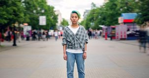 Zoom out time lapse of stylish Asian teen standing in pedestrian street alone stock video footage