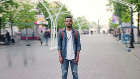 Zoom-out time lapse of young man Arab standing in busy street with backpack. Zoom-out time lapse of attractive young man Arab standing in busy street with stock video