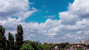 Zoom out timelpase of fast moving clouds over trees and apartment buildings in the city. Scene in Europe stock footage