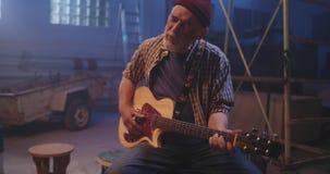 Mature man playing guitar in hangar