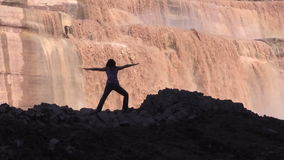 Zoom out of a Woman Practicing Yoga at Grand Falls stock video