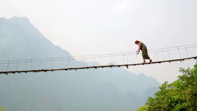 Zoom,Pan,Tourist woman crossing dangerous bamboo suspension bridge stock video