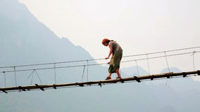 Zoom,Pan,Tourist woman crossing dangerous bamboo suspension bridge stock footage