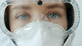 Zoom-in portrait of serious woman doctor wearing safety uniform mask, suit and respirator