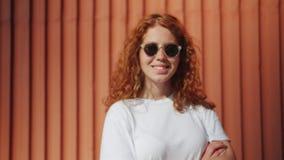 Zoom-in-Portrait von Rotkopfmädchen in Sonnenbrillen, die im Freien neben der Wand stehen stock video footage