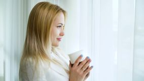 Zoom in of pretty blonde woman day dreaming near big curtained window with a cup. In slow motion. young caucasian female in modern interior. privacy, joy and stock video