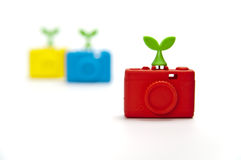 Zoom in red silicon compact camera with green leaf. On top Stock Images