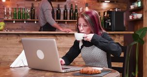 Zoom in shot on mature businesswoman in her 40s working on laptop. In vintage and stylish coffee shop, pub or restaurant stock footage