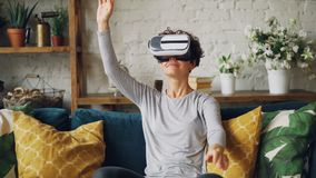Zoom-in of smiling young lady in augmented reality glasses moving hands and turning head sitting on sofa at home and. Having fun. Entertainment and modern stock footage