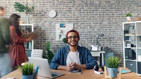 Zoom in time-lapse of happy business owner looking at camera smiling in office stock footage