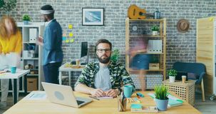 Zoom-in time lapse portrait of young entrepreneur sitting at desk in office
