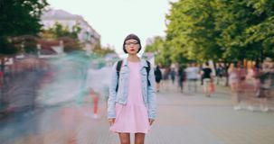 Zoom in time lapse of pretty teenager standing in street with backpack stock video