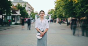 Zoom in time lapse of serious woman in casual clothing standing in busy street. Zoom in time lapse of serious young woman in casual clothing standing alone in stock video footage