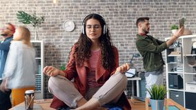 Zoom in time-lapse of woman listening to music in lotus pose on office desk stock video footage