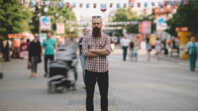 Zoom in timelapse of Young bearded man standing still at sidewalk in crowd traffic with people moving fast stock footage