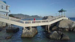 Zoom to Girl on White Stone Bridge across Rocks stock footage