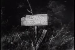 Zoom in to Trespass At Your Own Risk sign stock footage