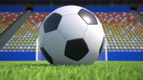 Zoom-ut till en fotbollboll som ligger på gräset i en tom stadion stock video