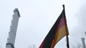 Zoom in video of Germany flag on pole. Zoom in video of Germany flag waving at wind on pole with factory plant chimneys on background. 4k footage stock footage